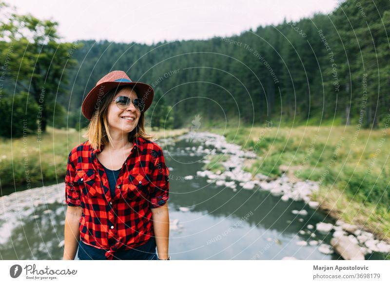 Junge Frau genießt die freie Natur am Fluss in den Bergen aktiv Abenteuer lässig Bach Fundstück Umwelt Expedition erkunden Entdecker Wald Freiheit Mädchen Hut