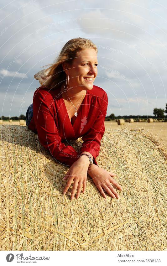 Junge Frau liegt auf einem Strohballen auf dem Feld und lächelt Freizeit Spaß Freude Jeans Ganzkörper Zentralperspektive Blick in die Kamera