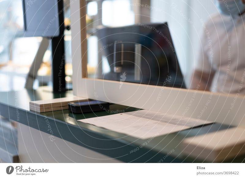 Eine Scheibe aus Plexiglas zum Schutz vor einer Ansteckung mit Corona | Corona Thoughts Barriere Absperrung Sicherheit Vermeidung Tresen Kasse Geschäft Büro