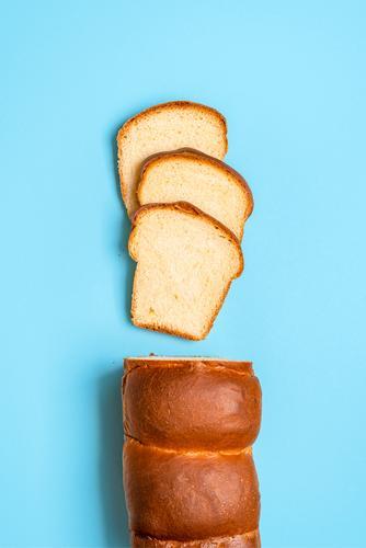 Geschnittenes Sandwichbrot mit Sauerteig. Hausgemachtes Milchbrot. Japanisches Brot obere Ansicht gebacken Bäckerei Blauer Hintergrund Brioche Butter Kruste