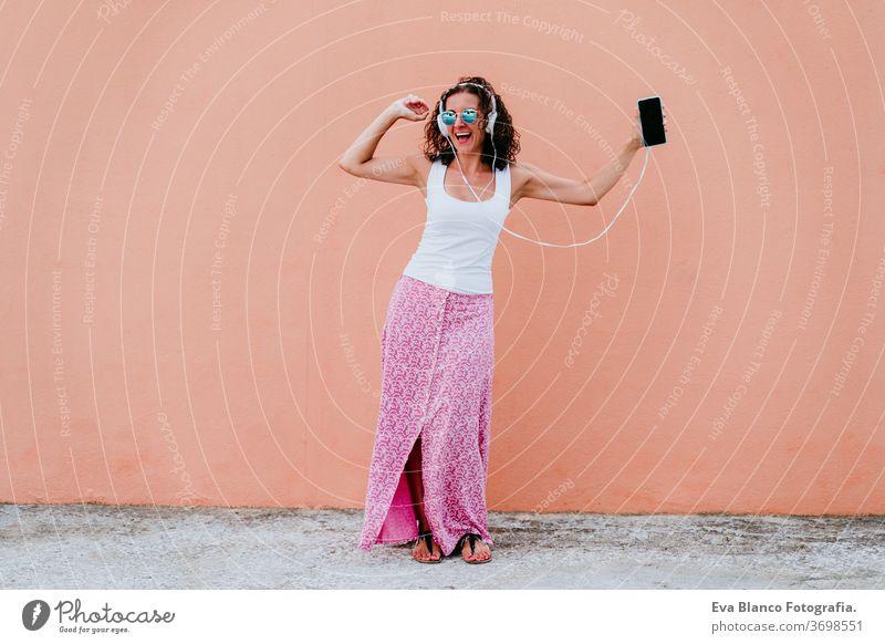 junge glückliche Frau im Freien, die über Kopfhörer und Mobiltelefon Musik hört. Lebensstil in der Stadt. Sommerzeit Handy hören Musik-Headset Großstadt urban