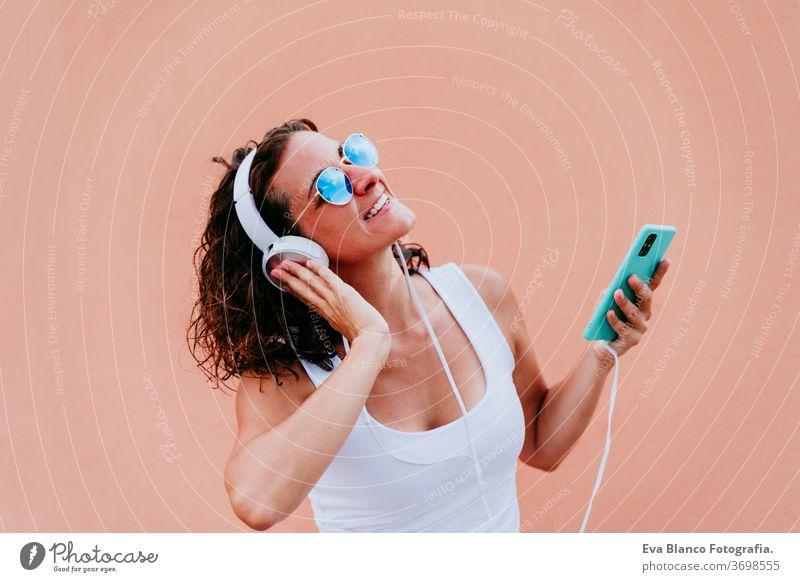 junge glückliche Frau im Freien, die über Kopfhörer und Mobiltelefon Musik hört. Lebensstil in der Stadt. Sommerzeit. Nahaufnahme Handy hören Musik-Headset