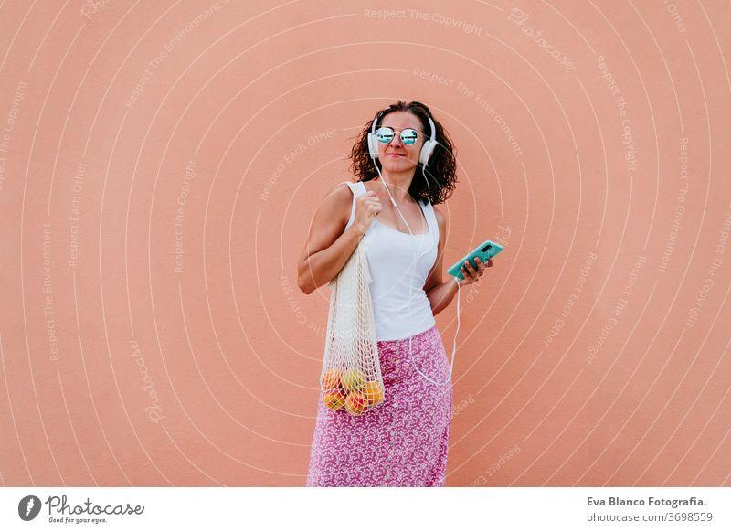 Frau, die ein Mobiltelefon benutzt, Musik über Kopfhörer hört. mit einem Baumwollbeutel mit Obst durch die Stadt läuft. Umweltfreundlich, Null-Abfall-Konzept