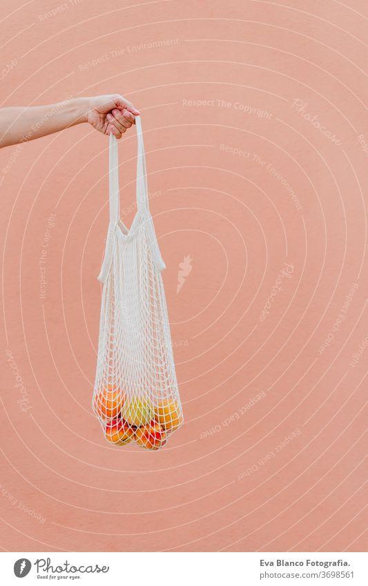 Frau hält Baumwollbeutel mit Obst. Umweltfreundlich, Null-Abfall-Konzept keine Verschwendung Beteiligung Baumwolltasche unkenntlich Großstadt urban Verbraucher