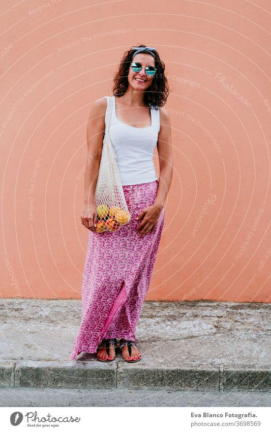 Frau, die durch die Stadt läuft und einen Baumwollbeutel mit Obst in der Hand hält. Umweltfreundlich, Null-Abfall-Konzept keine Verschwendung Kaukasier