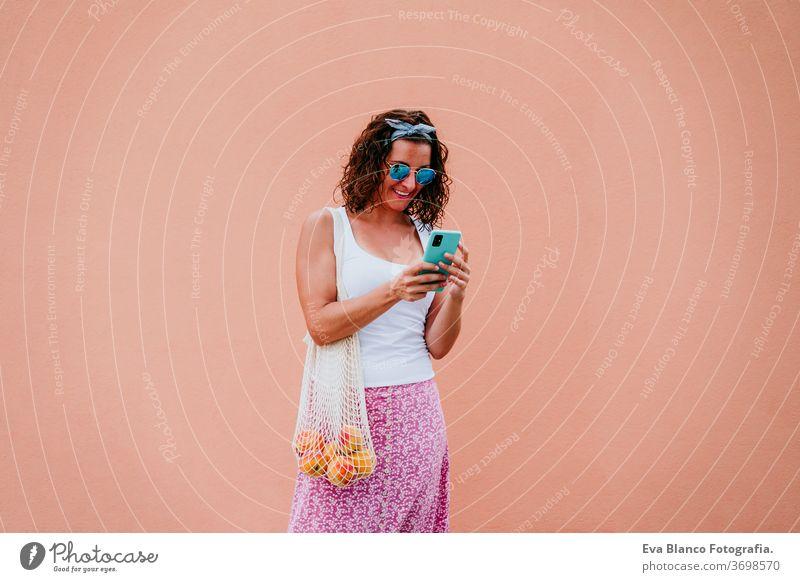 Frau, die durch die Stadt läuft, ein Mobiltelefon benutzt und einen Baumwollbeutel mit Obst in der Hand hält. Umweltfreundlich, Null-Abfall-Konzept