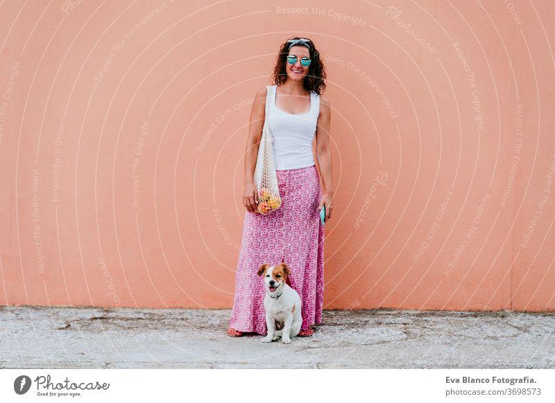 Frau niedliche Hündin, die durch die Stadt spaziert und eine Baumwolltasche mit Obst hält. Umweltfreundlich, Null-Abfall-Konzept Hund Haustier