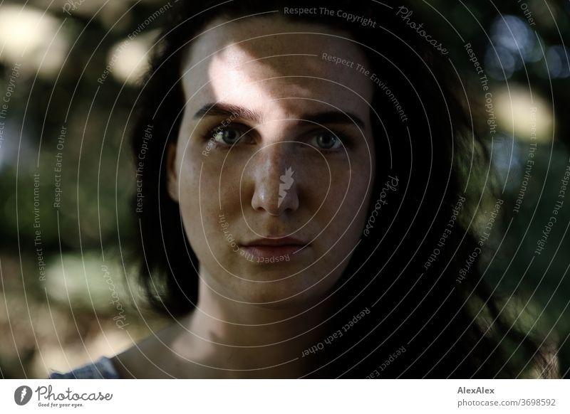 Nahes Portrait einer sommersprossigen Frau in einem Wald im Sommer zart Schatten Licht sportlich feminin Empathie Gefühle emotional Blick in die Kamera Porträt