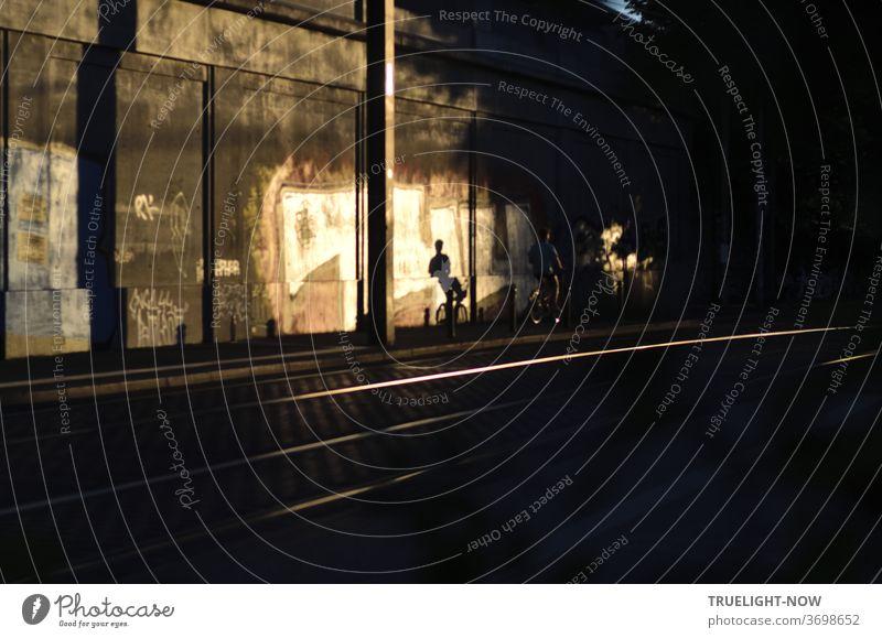 Ein Radfahrer verschwindet neben den aufblitzenden Bahngleisen in der Dunkelheit, doch die tief stehende Abendsonne wirft seinen sportlichen Schatten auf die von den letzten Sonnenstrahlen angeleuchtete Betonmauer