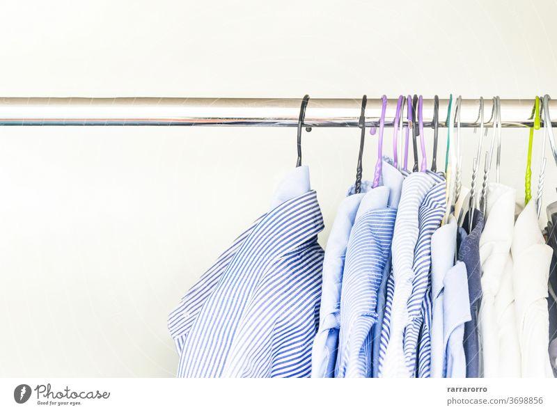Eine Gruppe von Herrenhemden in verschiedenen Farben, die mit Kleiderbügeln in einem Schrank aufgehängt sind Hemd erhängen Kleiderschrank Baumwolle Gewebe