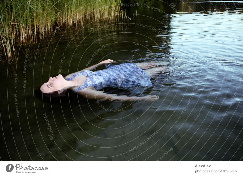 Portrait einer Frau die in einem See treibt vor einem Ufer mit Schilf zart Licht sportlich feminin Empathie Gefühle emotional Blick in die Kamera Porträt