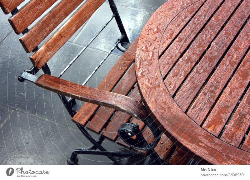 Im Regen stehen gelassen Tisch Stuhl Holz Möbel Sitzgelegenheit Stuhllehne Holzstuhl braun nass Regentropfen Gartenmöbel Biergarten außengastronomie Terrasse