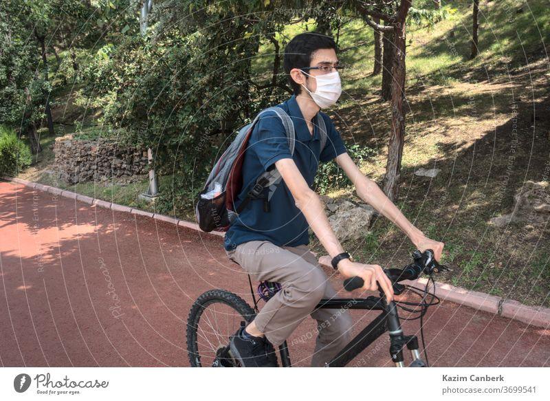 Isoliert und maskiert fahrender junger Mann auf einem Fahrrad in einem öffentlichen Park Korona Coronavirus Virus weltweit Seuche Pandemie Person Mundschutz