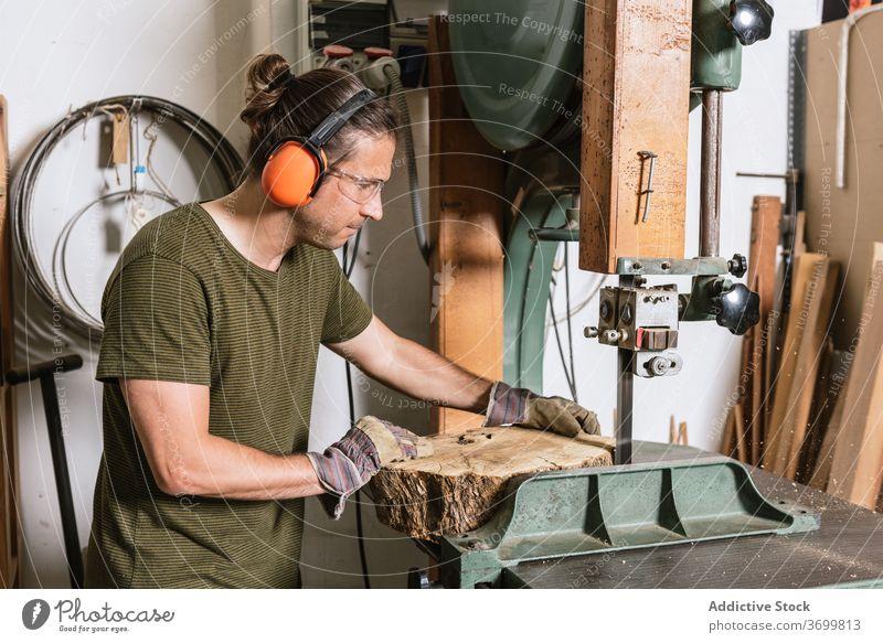 Männlicher Holzarbeiter schneidet Holz in der Werkstatt geschnitten Bandsäge Zimmerer Mann Tischlerin Holzarbeiten professionell männlich Nutzholz Säge schäbig