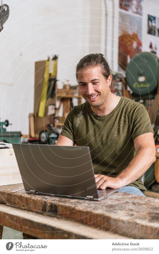 Lächelnde männliche Holzarbeiter mit Laptop in der Werkstatt Holzarbeiten Zimmerer Mann Projekt Arbeit benutzend Hobelbank Inhalt Netbook modern Gerät