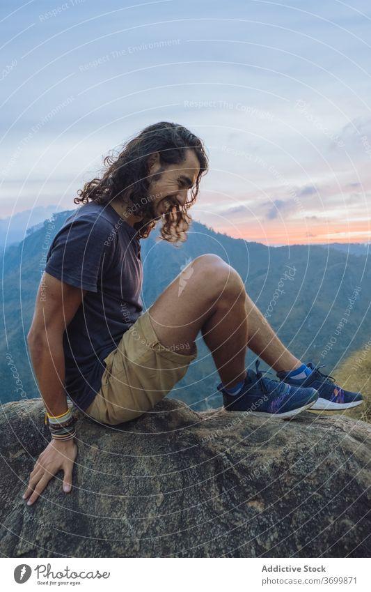 Mann sitzt auf dem Rand eines Bergfelsens und bewundert die Aussicht Reisender Berge u. Gebirge Sonnenuntergang heiter bewundern Landschaft erstaunlich Glück
