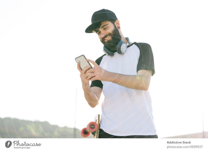 Sorgloser männlicher Skater, der in der Stadt auf seinem Handy surft Hipster Longboard Straße Mann Smartphone Wochenende genießen benutzend soziale Netzwerke