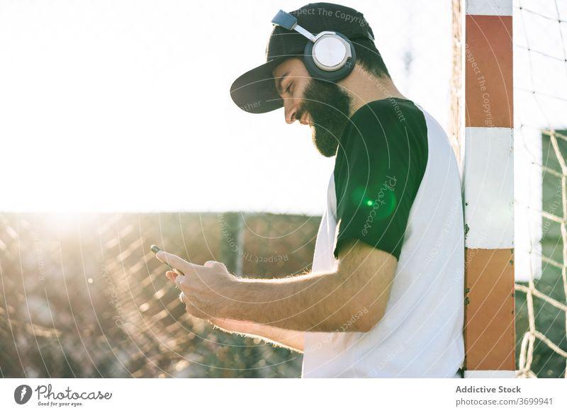 Zufriedener Mann, der mit Kopfhörern Musik hört zuhören Hipster Smartphone Talkrunde soziale Netzwerke benutzend Sommer männlich Mobile Internet Anschluss