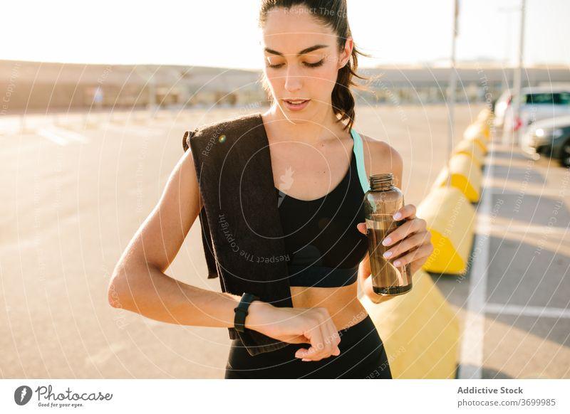Junge Sportlerin überprüft Fitness-Tracker nach dem Training auf der Straße prüfen Armband App passen schlank trinken Wasser ruhen benutzend Gerät aktiv jung