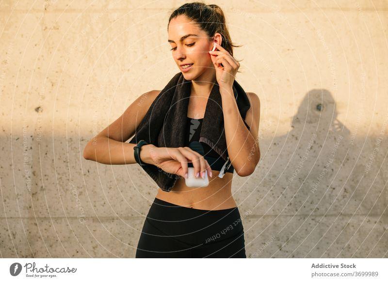 Sportliche Frau mit Kopfhörern und Fitness-Tracker ruht in der Nähe der Wand Sportlerin prüfen Armband App passen schlank Straße Training benutzend Gerät aktiv