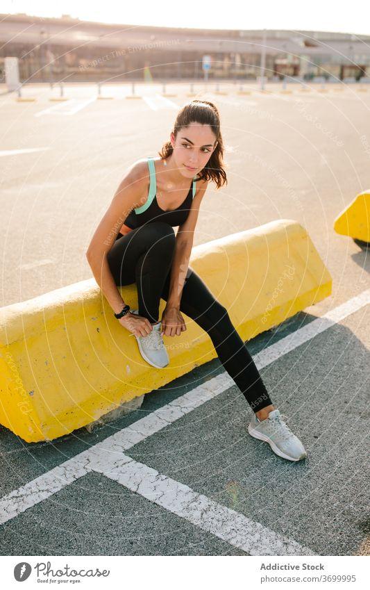 Sportliche Frau binden Schnürsenkel auf Turnschuhe vor dem Training Sportlerin Krawatte Schuhbänder vorbereiten Läufer sportlich Straße passen Athlet aktiv jung