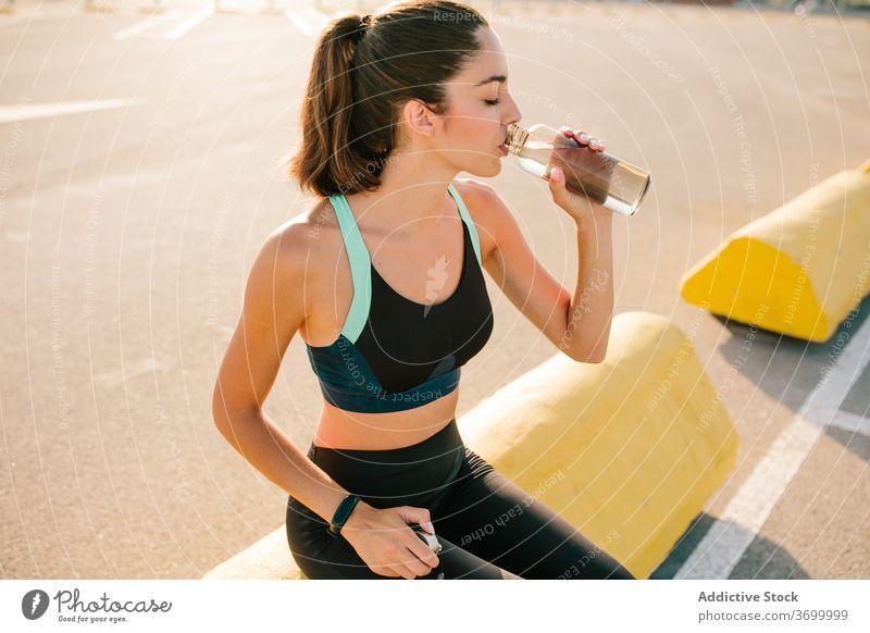 Junge sportliche Frau mit Getränkeflasche auf der Straße trinken ruhen passen Augen geschlossen positiv aktiv Training Erfrischung Energie jung Flasche