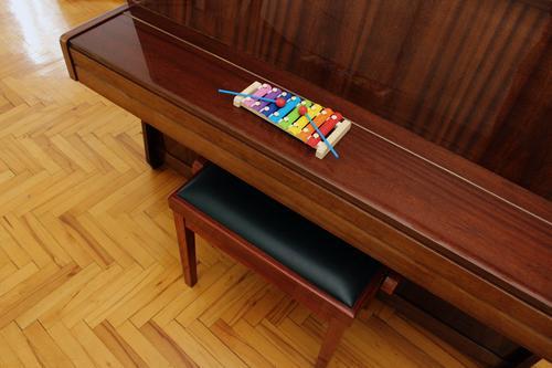 Draufsicht auf ein Spielzeugxylophon und ein klassisches Klavier auf Holzfußboden in Innenaufnahme. Xylophon oben Top stehen Keyboard aufrecht Klassik