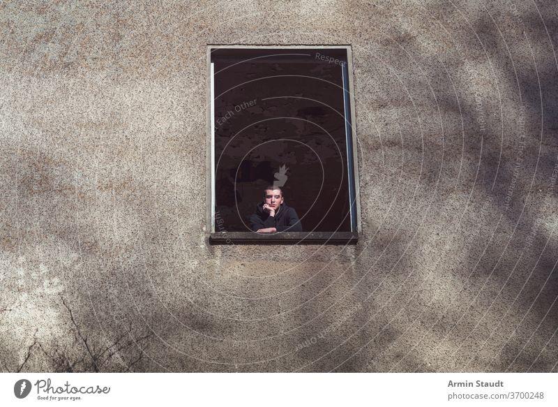 Junger Mann in einem verfallenen Haus schaut aus dem Fenster jung Blick alt Kinn Hand Architektur Ruine Person männlich Verlassen Kaukasier Porträt Gebäude Wand