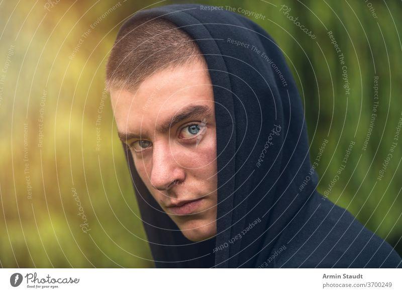 Porträt eines ernsthaften jungen Mannes in einem schwarzen Kapuzenpulli Aussehen Teenager Blick männlich schön lässig Kaukasier im Freien selbstbewusst Model
