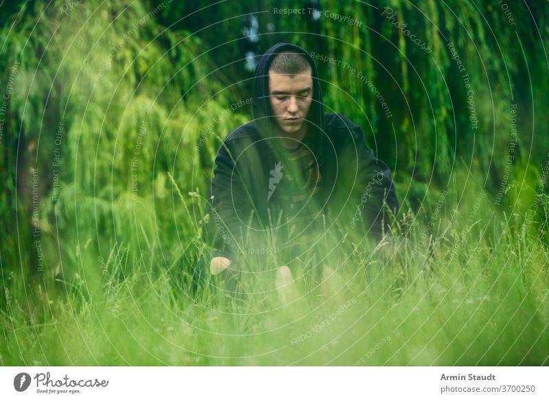 Porträt eines traurigen, kauernden Mannes in einem schwarzen Kapuzenpulli jung ernst Sorge hockend Wiese Natur Sommer Aussehen Teenager Blick männlich schön