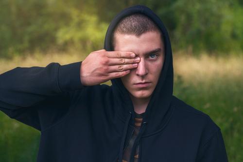 Bildnis eines jungen Mannes mit einem schwarzen Kapuzenpulli, der seine Augen verdeckt Porträt ernst deckend Hand Finger Aussehen Teenager Blick männlich schön