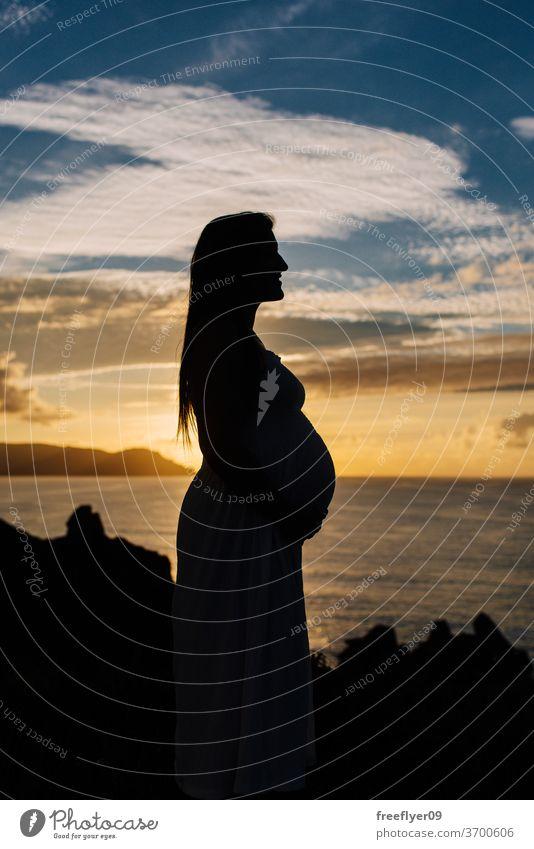 Silhouette einer schwangeren Frau vor einer ozeanischen Landschaft Profil Seitenansicht Textfreiraum dunkel schwarz Hintergrundbeleuchtung Sonnenuntergang
