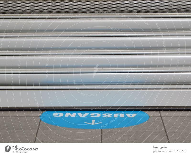 """Blauer Aufkleber mit weißer Schrift """"AUSGANG"""" und weißem Pfeil auf dem Boden vor einem geschlossenen Geschäft Ausgang Schilder & Markierungen Hinweisschild"""