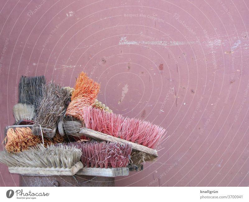 Eine Sammlung alter Straßenbesen hochkant in einem Metalleimer vor rostbrauner Wand Besen Sauberkeit Reinigen Kehren dreckig Arbeit & Erwerbstätigkeit