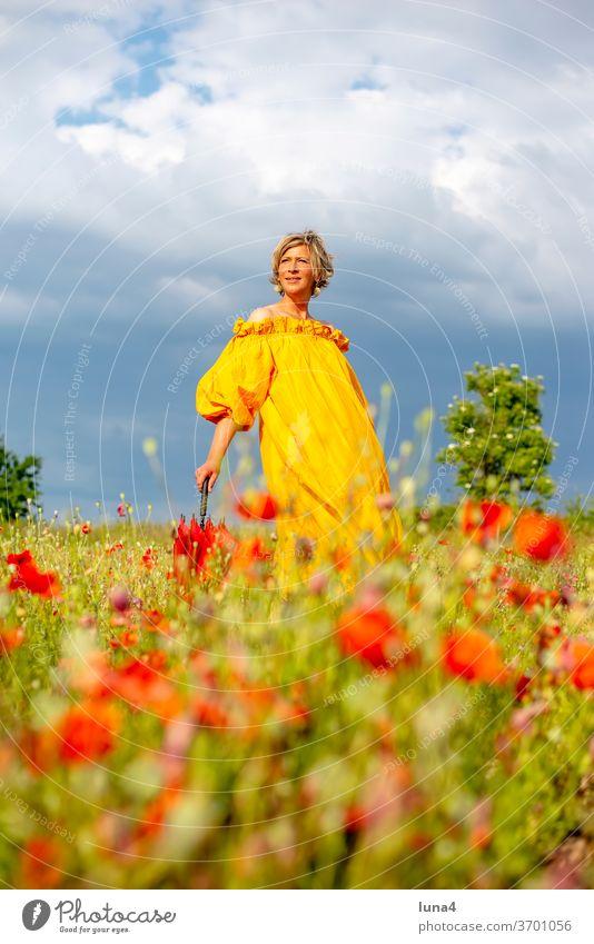 Frau mit Schirm auf Blumenwiese Mohn lachen junge Frau Mohnfeld Wiese Regenschirm spazieren glücklich fröhlich Auszeit Glück Freude Frühling Kleid laufen