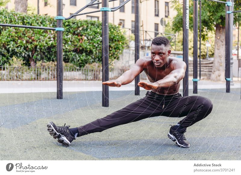 Starker Sportler macht Ausfallschritte auf der Straße Mann Übung Training sportlich Athlet stark ohne Hemd muskulös Sportpark männlich Afroamerikaner schwarz