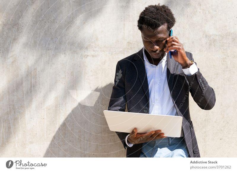 Seriöser Geschäftsmann spricht am Handy in der Stadt diskutieren Arbeit Smartphone reden Manager Exekutive Laptop benutzend Business männlich ethnisch schwarz