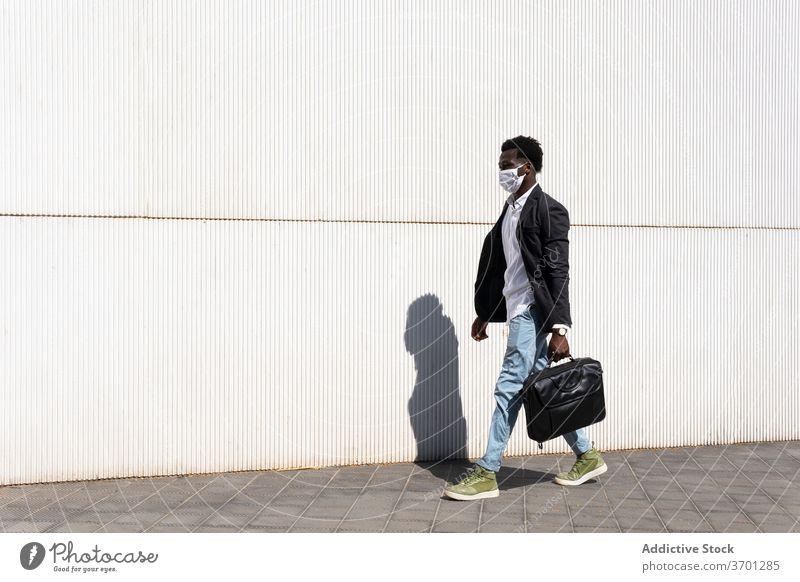 Selbstbewusster ethnischer Geschäftsmann beim Gehen auf der Straße medizinisch Mundschutz Großstadt Spaziergang Seuche Coronavirus Unternehmer behüten männlich
