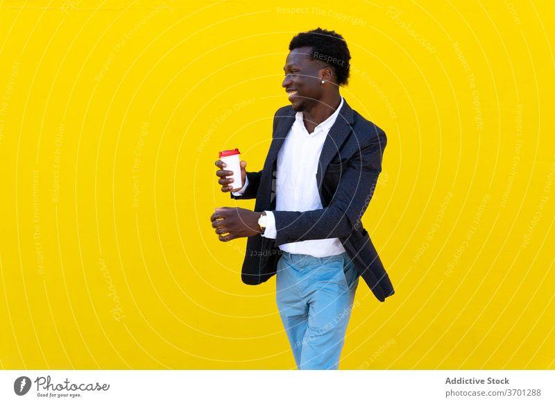 Lächelnder ethnischer Geschäftsmann in der Stadt Imbissbude Kaffee Mann Großstadt heiter Unternehmer zum Mitnehmen gut gekleidet Straße männlich Afroamerikaner