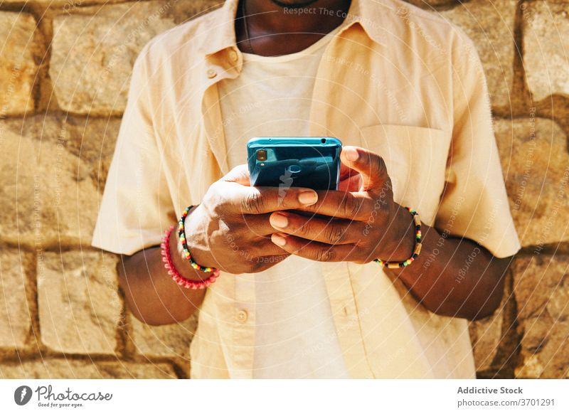Anonymer ethnischer Mann mit Smartphone Talkrunde soziale Netzwerke unterhalten Wochenende benutzend Nachricht Großstadt männlich schwarz Afroamerikaner