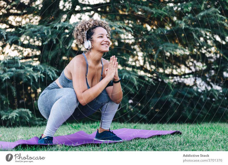 Energetische junge Frau Training im Park Fitness Übung Kniebeuge sportlich heiter Energie Kopfhörer Gesundheit Sportbekleidung Wellness passen ethnisch