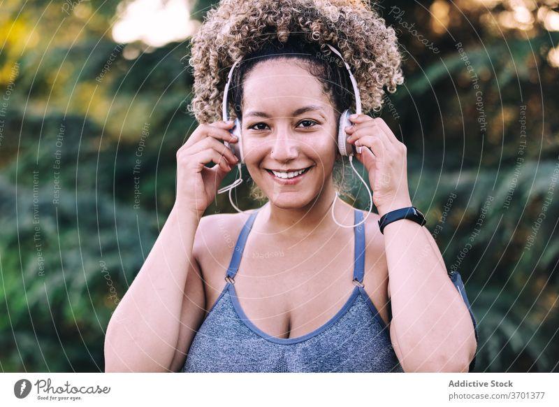 Fröhliche Sportlerin beim Musikhören mit Kopfhörern im Park Frau sportlich zuhören Glück heiter Fitness genießen ausrichten Energie jung Smartphone Training