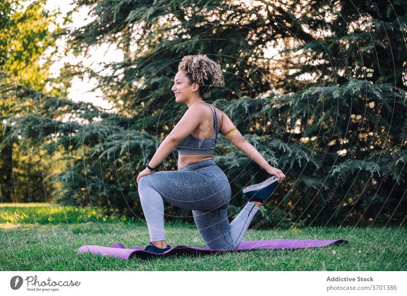Fit Frau Stretching Beine während des Trainings im Park Übung Dehnung Ausfallschritt Fitness sportlich heiter jung Gesundheit Sportbekleidung Wellness passen