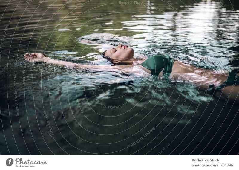 Serene Frau schwimmend auf See Wasser Schwimmer genießen Urlaub Gelassenheit sich[Akk] entspannen Teich Bikini Sommer Lügen Augen geschlossen Badebekleidung