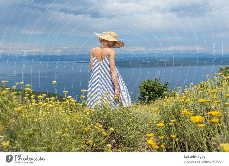 Rückansicht einer jungen Frau in gestreiftem Sommerkleid und Strohhut, die in einer Superblüte von Wildblumen steht und sich entspannt, während sie einen schönen Blick auf die Natur der Adria genießt, Kroatien