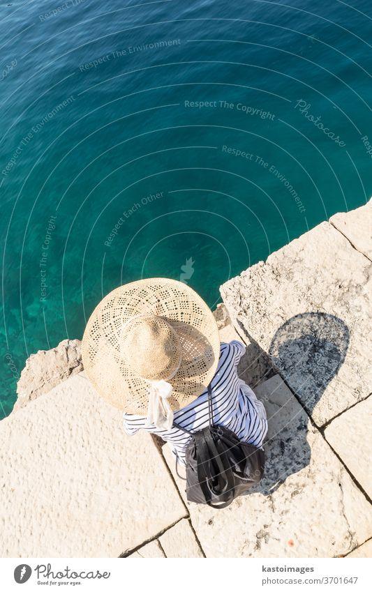 Grafische Darstellung der Draufsicht einer Frau mit großem Sommersonnenhut, die sich am Pier am klaren türkisfarbenen Meer entspannt. Wasser Sonne Hut Freizeit