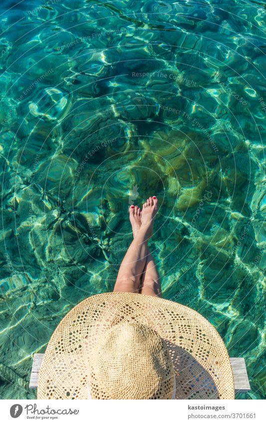 Grafische Darstellung der Draufsicht einer Frau mit großem Sommersonnenhut, die sich auf einem kleinen Holzsteg am klaren türkisfarbenen Meer entspannt Wasser