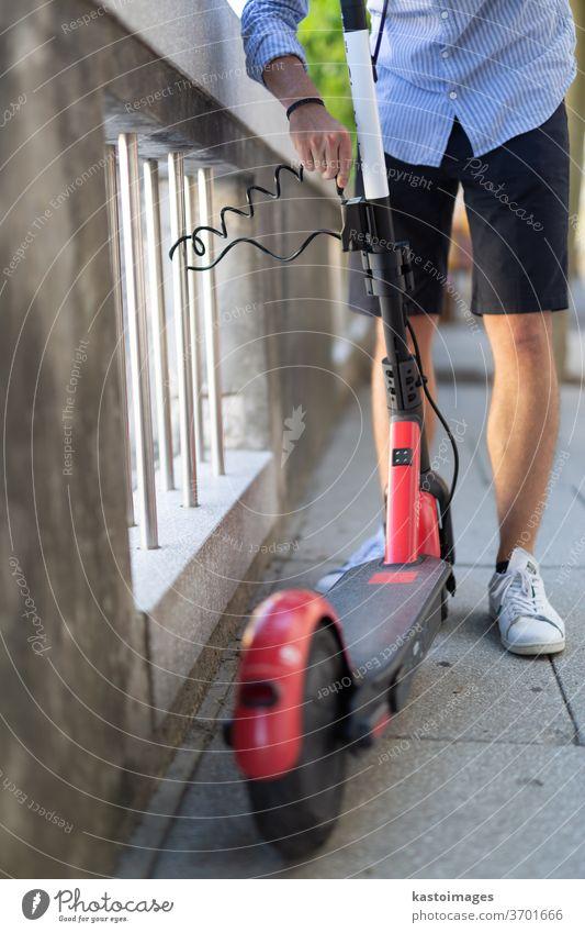 Männlicher Benutzer parkt Elektroroller sicher und verriegelt ihn an einem Zaun. Umweltfreundliches, grünes, modernes städtisches Mobilitätskonzept zur gemeinsamen Nutzung von Verkehrsmitteln mit Elektrorollern zur Miete in Ljubljana, Slowenien
