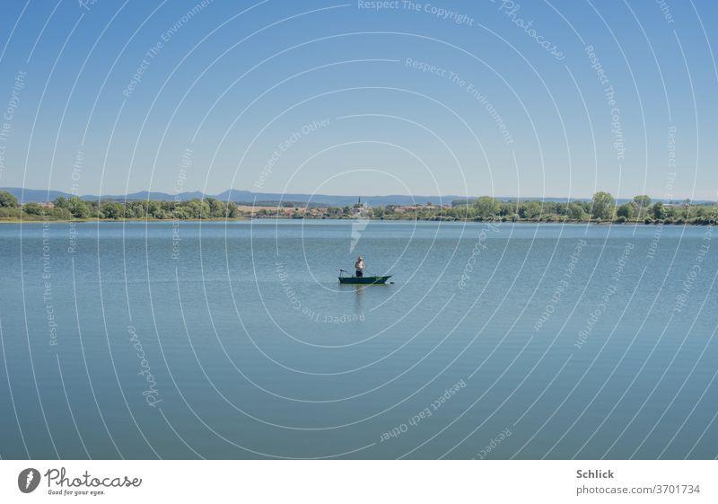 Ein einzelner  Angler in seinem Boot auf einem See Dorf Kirche ländlich blau Landschaft einsam still Stille Ortschaft Lothringen Kanal Wasser Horizont Ruhe