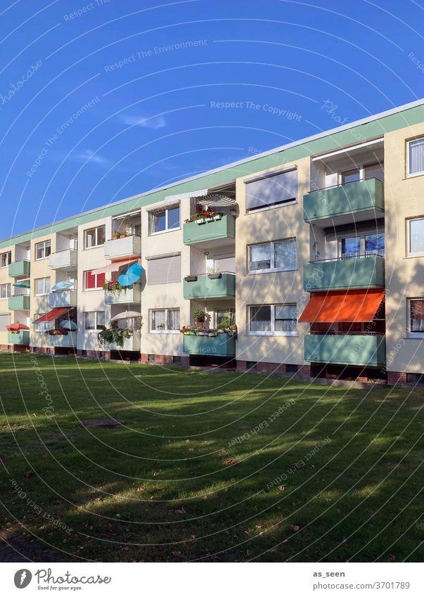 Urlaub auf Balkonien Sonnenschirm Balkone Architektur 50er Jahre sozialer Wohnungsbau Haus Fassade Gebäude Stadt Farbfoto Fenster Tag Menschenleer Außenaufnahme